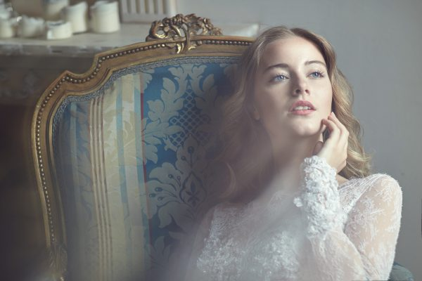 Model Bride in the studio sitting on a chair in the sunshine. Beauty, glow, tenderness.